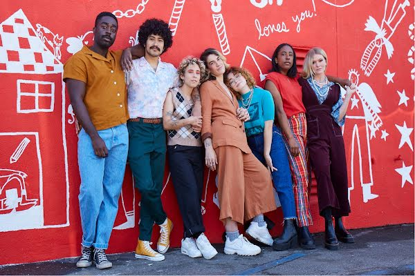 A diverse group of young LGBTQ+ people gather for a relaxed portrait in front of a vibrant red street art wall