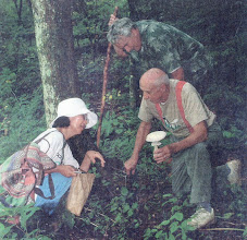 Photo: Dick Grimm showing Yunhwa Brann & Jim Wagner an Agaricus Mushroom circa 2004. Photograph by Aurthur Brown of the News Journal.