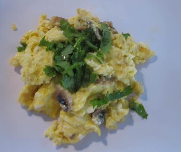 Scrambed Eggs With Mushrooms And Feta Cheese, Topped With Cilantro.