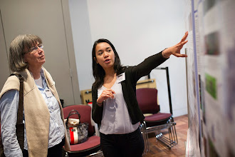 "Photo: Ain Roesley (St Vincent's Institute) explaining her poster, ""Control of cell proliferation by Brahma chromatin-remodelling complex"" to Emma Whitelaw, one of the plenary speakers"