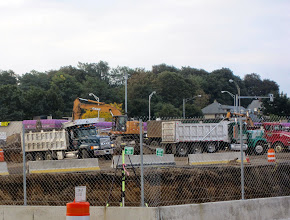 Photo: Lines of trucks removing fill from Wegmans site.