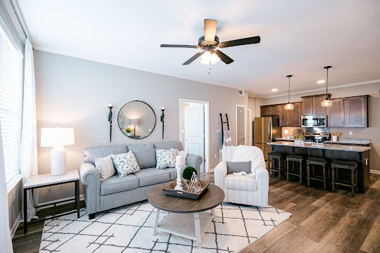 Fully-furnished model unit living room and kitchen areas with wood plank flooring, gray walls, and a ceiling fan