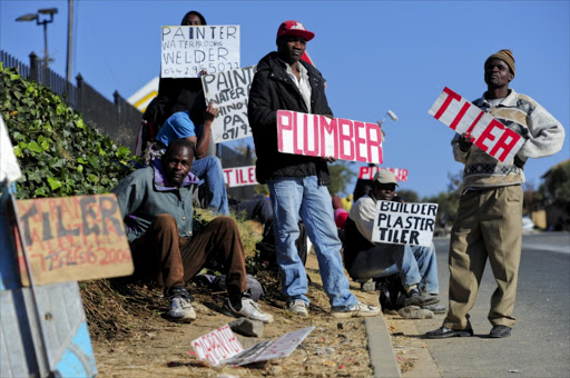Unemployed painters, plumbers and tilers wait outside Builder's Warehouse in Johannesburg, South Africa, for job opportunities on June 6, 2012.