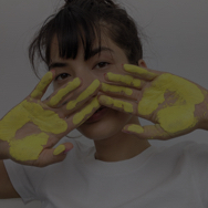 Woman holding up hands against face, with yellow paint on both palms