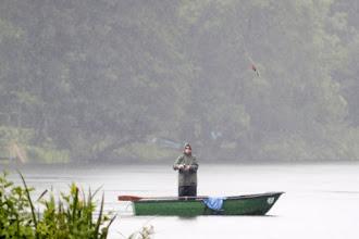 Photo: Angler wirft im Regen von seinem Boot auf dem Großensee die Angelschnur aus