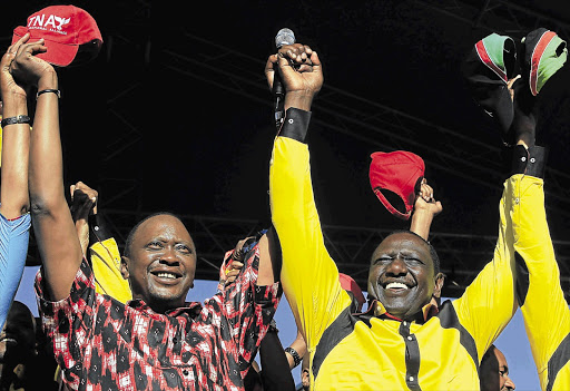 Kenya's Deputy Prime Minister Uhuru Kenyatta (left) and his running mate, former cabinet minister William Ruto, wave to their supporters during a rally in Nairobi last month. Both have been indicted by the ICC for crimes against humanity