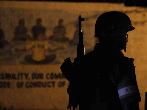 An Amisom soldier helps the police in Mogadishu, Somalia. /MONICAH MWANGI