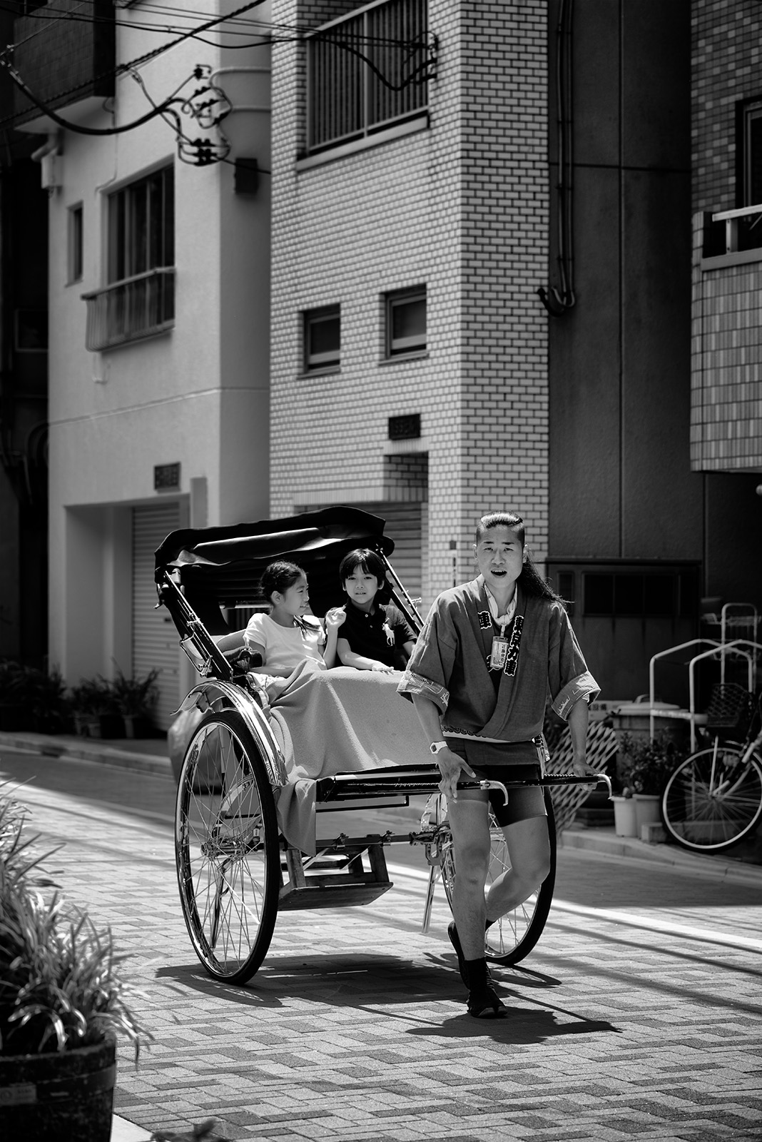 "Photo: Jinrikisha  Yes, another one from the #GPlus2YearAnniversary  photowalk.  Almost finished going through them though.  (^^;  I've seen these ""jinrikisha"" around the Asakusa area, but though it looks like fun, I've never tried it riding in one myself.  I know it's odd because it's their job, but I would always feel sorry for someone who had to pull me around! That, and it's a little expensive...  Off to bed, good night from Tokyo!  Settings: D800E / 105mm / f4 / ISO 100 / 1/500s  #Japan   #Tokyo   #Asakusa   #Jinriksha"