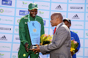 Athletics South Africa president Aleck Skhosana presents trophy to Justin Kemboi Cheshire (L), winner of the 2018 Old Mutual Two Oceans 56km Ultra Marathon.