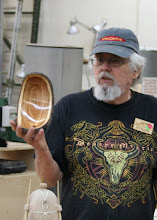 Photo: Here Ed shows off a natural edge bowl from plum wood. He brought in pieces of this plum and the hybrid elm for the silent auction table.