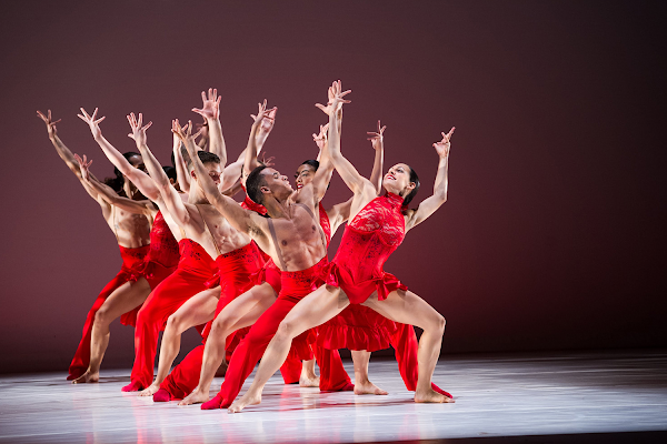 Modern ballet dancers on stage in red costumes.