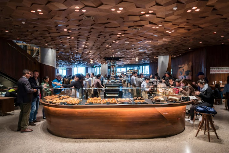 Visitors wait for their coffee at the Starbucks Reserve Roastery outlet in Shanghai on December 6, 2017.