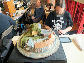 "Photo: 006 Simon Hargreaves with his very neat HOm 12mm gauge maxi-pizza continental tram layout that was not named in the show guide, but from my memory of it appearing at ExpoNG 2012, it was then called ""Leftover Light Railway"". Tim Sanderson does a turn guarding the teacups in the background ."