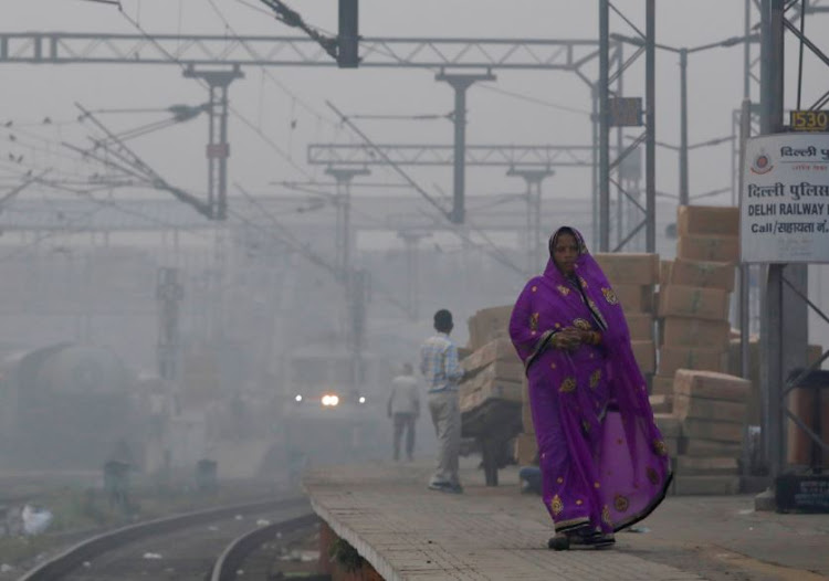 A woman walks along a railway platform on a smoggy morning in New Delhi, India, November 10, 2017.