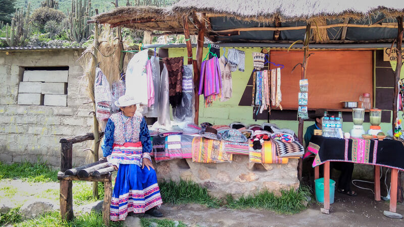 traditionally dressed peruvian women sitting outside a souvenir shop in mirador la cruz del condor in colca canyon arequipa peru
