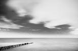 donkere wolken boven zee, waarin een palenrij