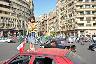 Photo: A girl holding an Egyptian flag stands atop a car in Tahrir Square on the day of the demonstration.