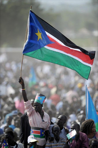 A man in a crowd carrying a South Sudan flag. File photo.