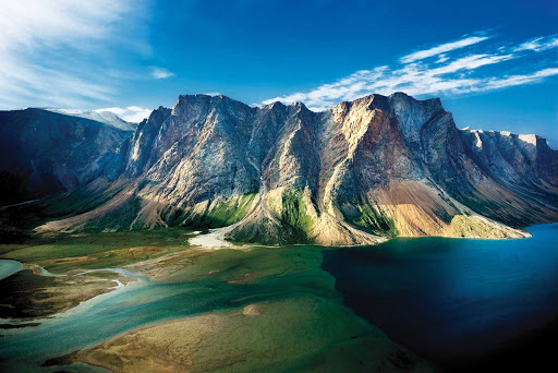View of a steep-sided mountain touched by blue waters at Torngat Mountains National Park at the northern tip of Newfoundland and Labrador.