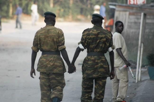 Two male soldiers in uniform are shown from behind walking and holding hands.