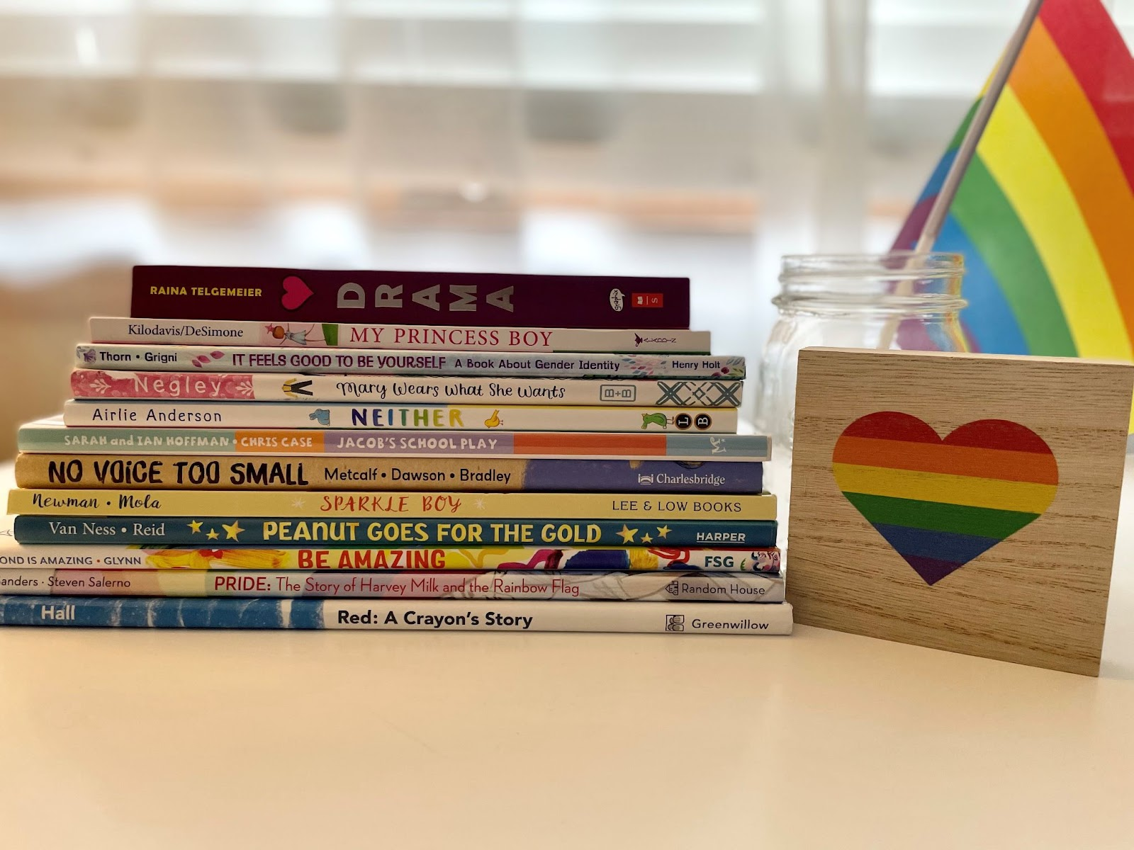 Stack of children's books with LGBTQ+ characters. Rainbow flag on right side of image.