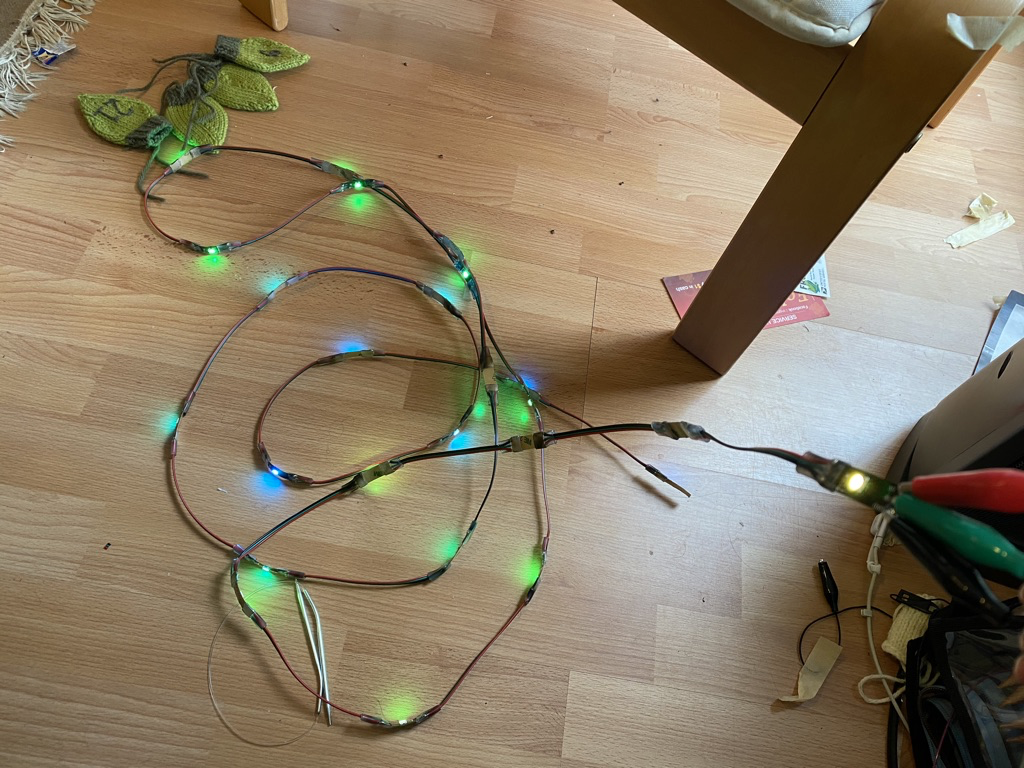 A coiled strip of illuminated LEDs connected to alligator clips, on a light wooden floor, with various objects in background