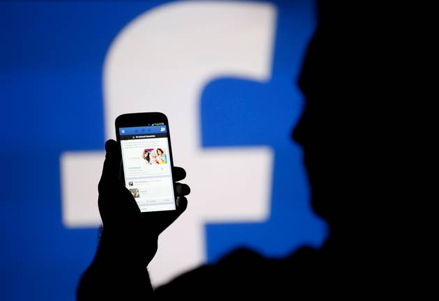 A man is silhouetted against a video screen with an Facebook logo. Facebook has admitted that social media may be a danger to democracy - due to how it aids the spread of misinformation.