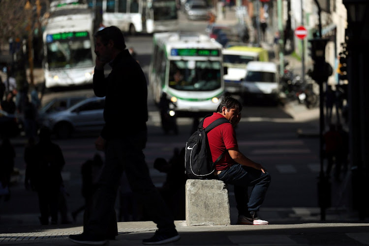A man sits down as people walk in Buenos Aires' financial district in Argentina.