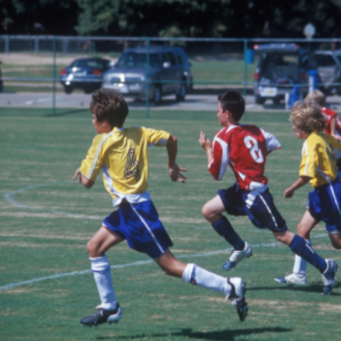 Young players running towards a ball