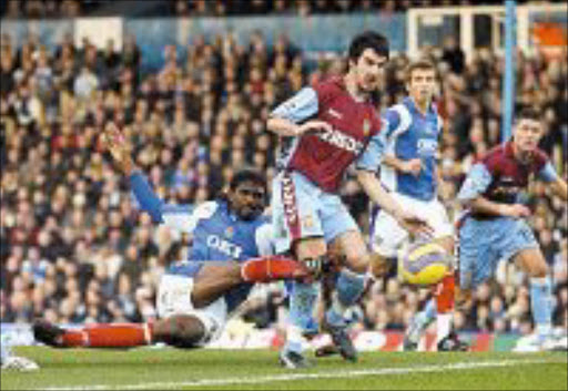 FLASHBACK: Portsmouth's Nwankwo Kanu, left, goes close despite the attention of Aston Villa's Liam Ridgewell. © Unknown.