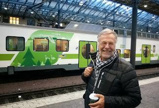 Photo: Iloinen junamatkailija asemalla aamutuimaan