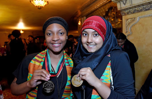Two young women with colorful scarves holding up medals.