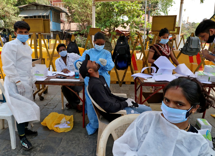 A health worker collects a swab sample from a man at a testing site in Mumbai, India, April 5 2021. Picture: REUTERS/NIHARIKA KULKARNI