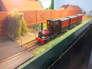 "Photo: 019 I didn't have time to enquire, but I thought the layout was a little light on stock running this time round. Perhaps it was because the layout has got so big, or perhaps somebody forgot to bring one of the stock boxes – we'll probably never know! Anyway, the one train that I did see running on both the occasions that I was able to see the layout, was this very nice steam passenger train – coaches from Peco 7mm scale NG modular components and the loco looks to me very much like a converted Grafar J94 saddle tank, but I was told that it is a pugbash, and the ""customer is always right"" so that's what it is then !"