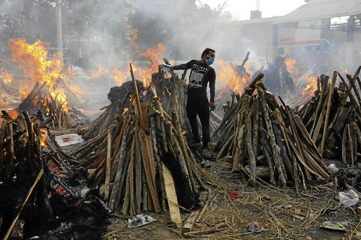 A man performs last rites next to the funeral pyres of people who died from Covid-19, during a mass cremation in New Delhi, India. The country experienced its deadliest day on Thursday this week, when 3,645 people died from the disease.