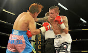 Hekkie Budler  thows a punch  at Phillipines  Joey Canoy during the  IBO junior flyweight fight. /Veli Nhlapo