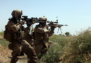 Photo: Sergeant Anthony Battles (left), Bravo Company, 1st Reconnaissance Battalion, 1st Marine Division (Forward), engages the enemy during a firefight in Northern Trek Nawa, Afghanistan, Aug. 15. The Marines and sailors of B Company are currently conducting counter insurgency operations in support of the International Security Assistance Force.