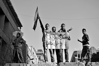 Photo: Youth raising a banner attacking both the ruling military junta and the Muslim Brotherhood.