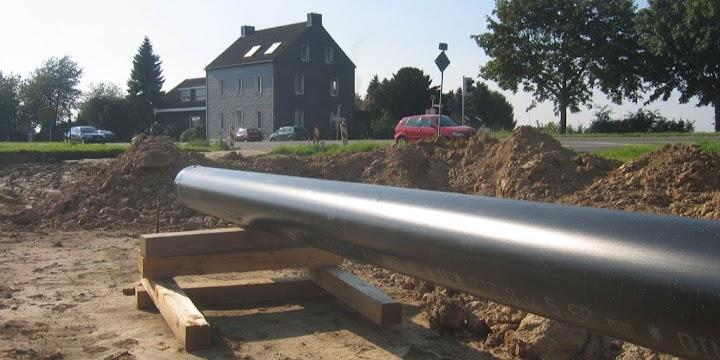 Rohrleitung, im Hintergrund Wohnhaus.