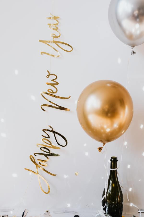 foto de uma garrafa de champanhe com balões dourados pendurados escrito happy new year