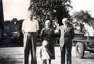 Photo: Tinus Hofsteenge met zijn dochter Lucie en zijn ouders Ede en Willempje Hofsteenge-Belt. Ze staan voor de smederij.