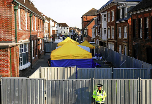 A police officer stands in front of screening erected behind John Baker House, where forensic tents are erected, after two people were poisoned with the nerve agent Novichok, in Amesbury, Britain, on July 5 2018. Picture: REUTERS