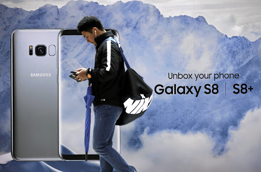 A man using his cellphone walks past an advertisement promoting a Samsung Galaxy S8 smartphone at a shop in Seoul. Picture: REUTERS