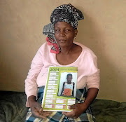Mmapholo Mono holds a picture of her daughter, Tlhalefo, whose remains were found in a toilet.  /Boitumelo Tshehle