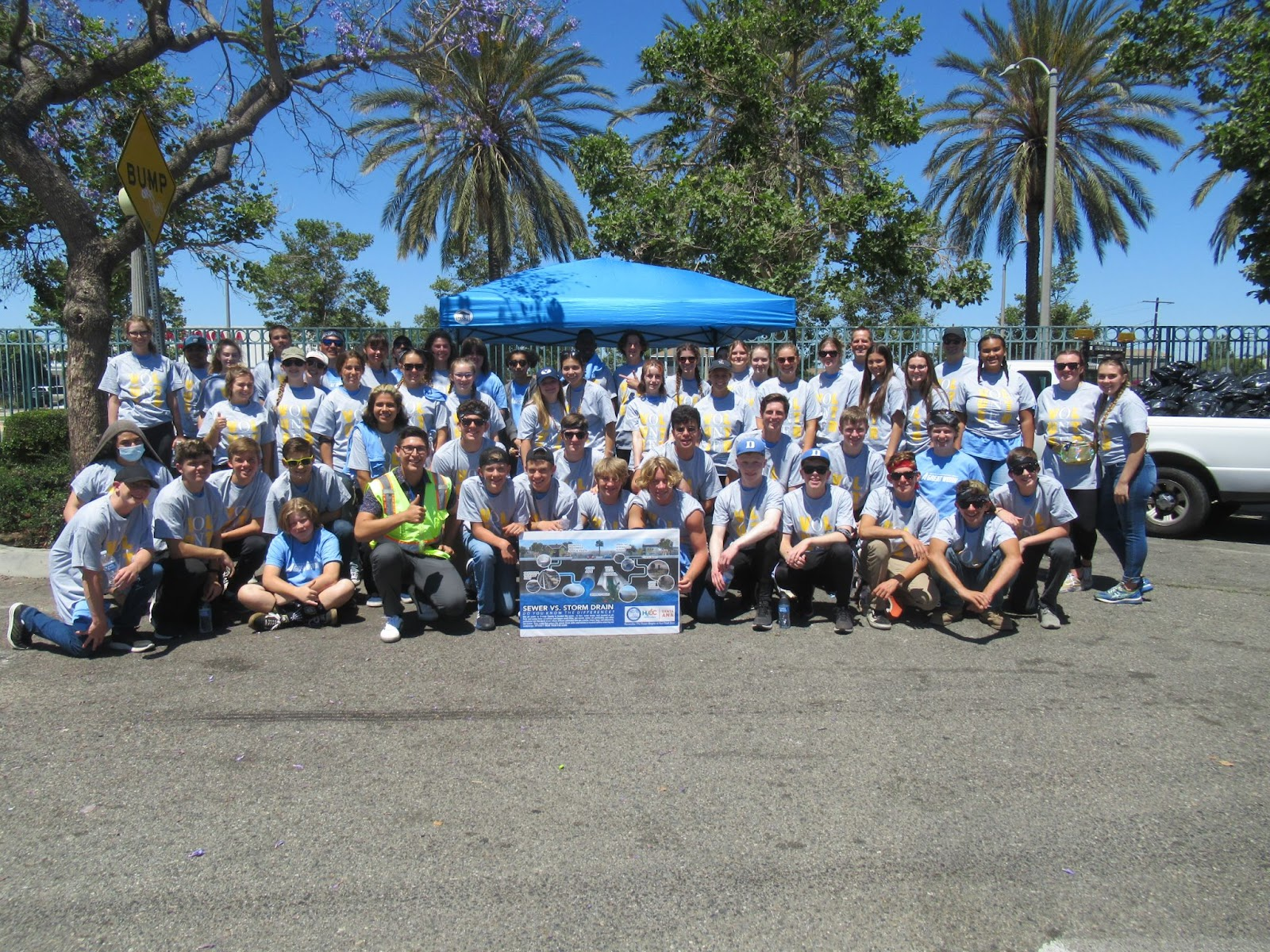 An image of over 50 people posing in front of a blue shade tent and some trees. They're all wearing grey and light blue shirts, and are all looking at the camera.