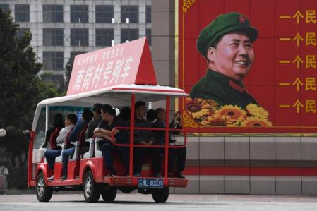 This photo taken on September 29, 2017 shows visitors riding a tourist cart past a billboard image of late communist leader Mao Zedong at a culture center in Nanjie village, in China's central Henan province. Every year, hundreds of thousands of visitors flock to the hamlet in central Henan province which has become an attraction with its idealised vision of village life right out of the Communist past. While the Communist Party prepares to give a second term to its current supremo, Xi Jinping, at a major congress next week, Nanjie still clings firmly to Mao, while glossing over the turbulence and violence of his rule. / AFP PHOTO / GREG BAKER / TO GO WITH AFP STORY CHINA-POLITICS-TOURISM,FOCUS BY BEN DOOLEY