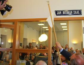 Photo: De wethouder onthult de naam van de zaal. Niet voor iedereen nieuw want vóór de verbouwing heette de zaal ook al zo. Het naambordje heeft de verbouwing overleefd.
