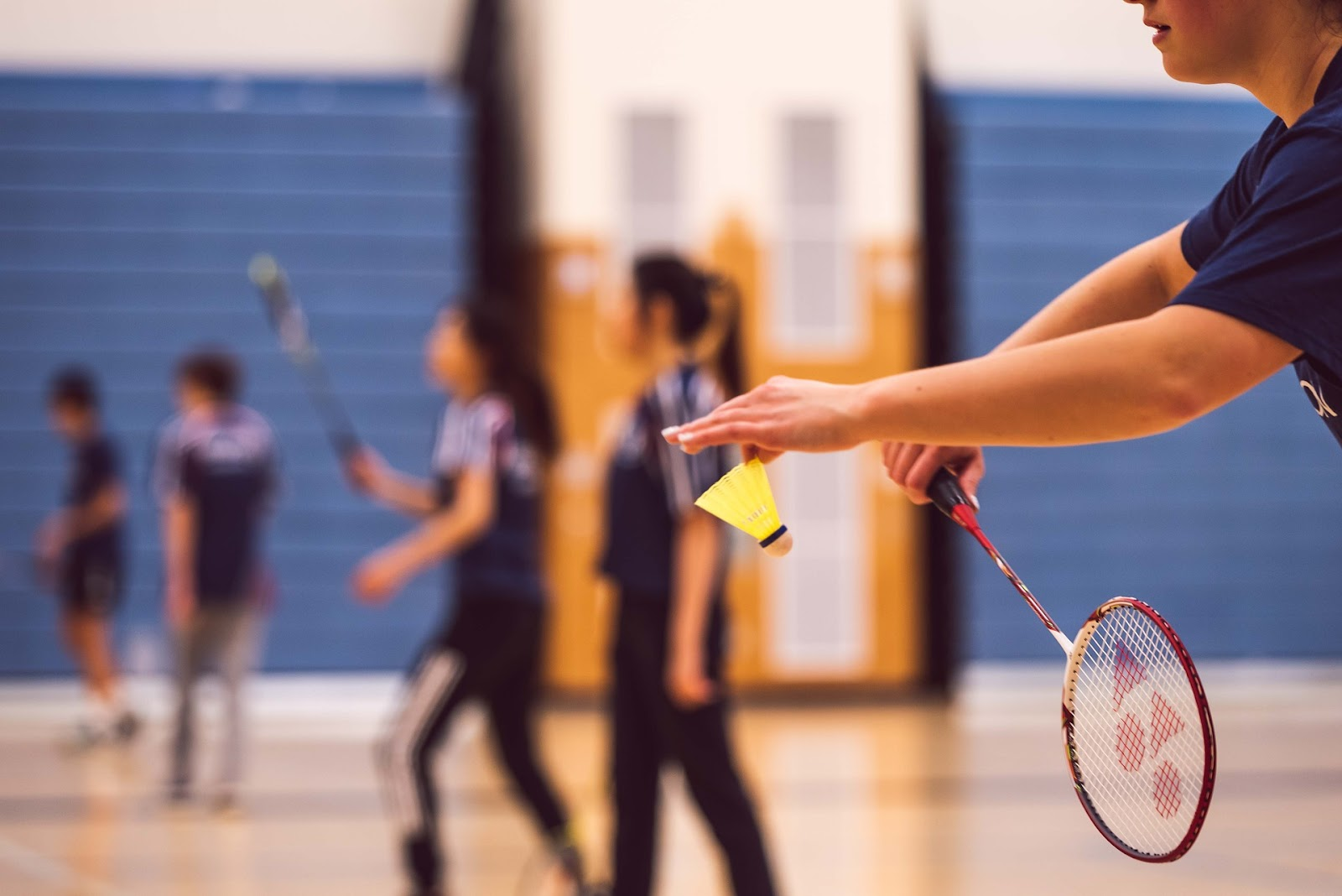 This is an image of a man holding a shuttlecock, preparing to serve with a badminton racket.