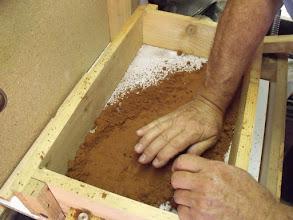 Photo: Le remplissage commence en tassant le sable sur la pièce......
