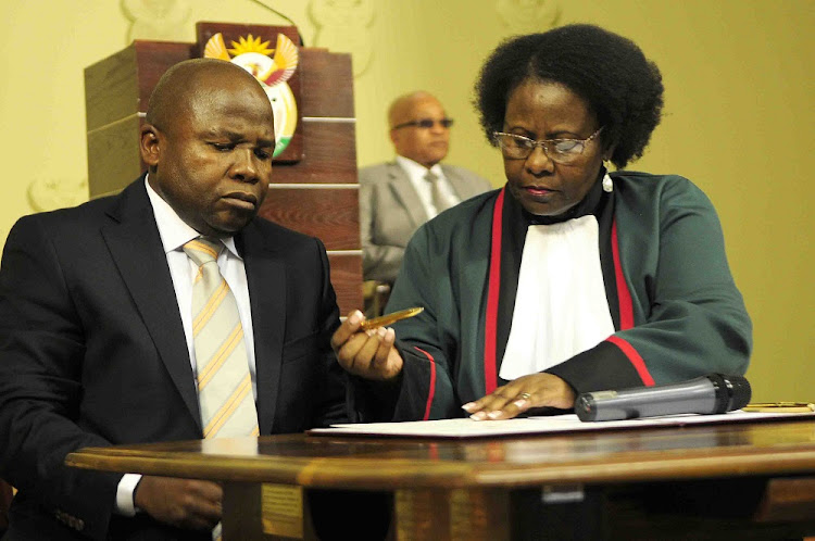 In this file image, former President Jacob Zuma can seen in the background during the swearing in ceremony of Des van Rooyen as then finance minister Judge Sisi Khampepe replacing Nhlanhla Nene on December 10 2015.